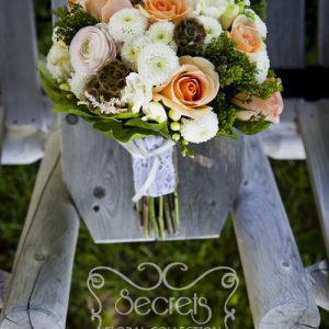 Fresh cream garden roses, peach roses, pink ranunculus, white freesia, scabiosa pods, green trachelium, white button mums, and pink astilbe bridal bouquet, with burlap and lace vintage wrap (front-view) - Toronto Wedding Flowers by Secrets Floral Collection