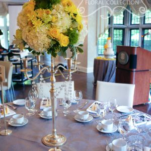 Fresh yellow roses, yellow cushion mums, green trick dianthus, light green carnations, succulents, cream hydrangea, yellow button mums, and dusty miller, on chrome candelabra with crystal strands