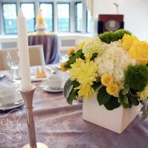 Fresh yellow roses, yellow cushion mums, green trick dianthus, light green carnations, succulents, cream hydrangea, yellow button mums, and dusty miller, in white cube pot