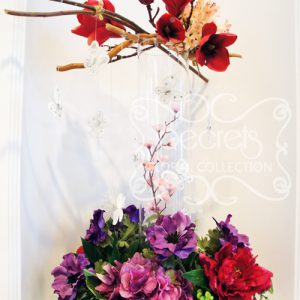 Artificial red mangolia, pink eremurus, pink cherry blossoms, fuchsia peonies, purple hydrangea, and purple anemones centrepiece with suspending butterflies (overview)