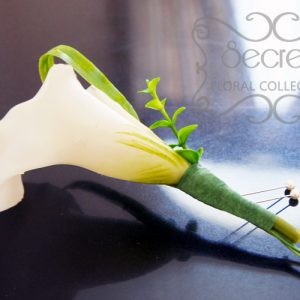 Artificial white calla lily boutonniere with boxwood leaves, lily grass, and double pearl pins (side-view) - Toronto Wedding Flowers Created by Secrets Floral Collection