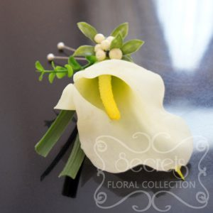 Artificial (soft-touch) white calla lily boutonniere with lily grass, boxwood leaves, ivory snow berries, and double pearl pins (top-view) - Toronto Wedding Flowers Created by Secrets Floral Collection