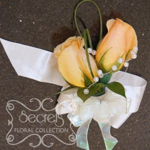 Fresh peach roses and bear grass bridesmaid wristlet with pearl embellishment (Front View) - Toronto Wedding Flowers Created by Secrets Floral Collection