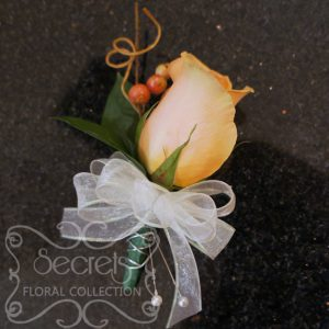 Fresh peach rose and red privet berries boutonniere with silver wire accent (Front View) - Toronto Wedding Flowers Created by Secrets Floral Collection