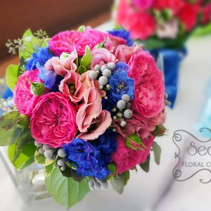 Fresh fuchsia garden roses, medium pink lisianthus,dark blue delphinium, silver brunia berries, and green seeded eucalyptus bridal bouquet, with a royal blue and sparkly mesh wrap (top-view) - Toronto Wedding Flowers by Secrets Floral Collection