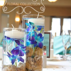 Pair of fresh blue dendrobium orchid centrepieces, submberged in water with seashells and floating candle