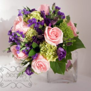 A bridal bouquet with lots of textures. Created with fresh light pink roses, purple lisianthus, baby green hydrangea, green trachelium, and purple statice flower (top view) - Toronto Wedding Flowers by Secrets Floral Collection