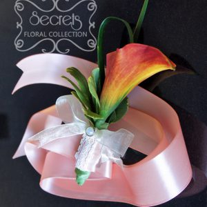 Fresh two-tone blood orange calla lily wristlet, with lace and pearl brooch on pink satin strap (front-view) - Toronto Wedding Flowers Created by Secrets Floral Collection