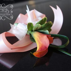 Fresh two-tone blood orange calla lily wristlet, with lace and pearl brooch on pink satin strap (top-view) - Toronto Wedding Flowers Created by Secrets Floral Collection
