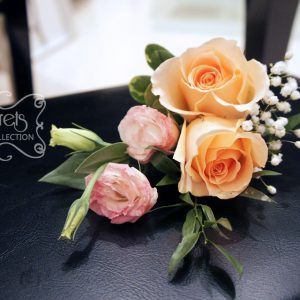 Fresh double-bloom peach roses, pink bi-colour lisisanthus, and baby's breath boutonniere, embellished with coral and white stripe-pattern ribbon (top-view) - Toronto Wedding Flowers Created by Secrets Floral Collection