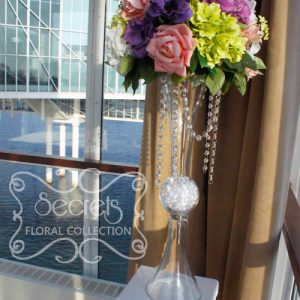 Artificial elevated arrangement, with salmon pink roses, pink agapanthus, purple anemones, (green, cream, lavender) hydrangea, and (green and white) lilac, embellished with crystal strands on reversible vase