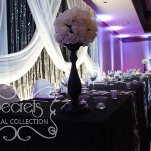 Head Table are Decorated with Ivory Ball on Black Stand Arrangements and Small Bling! Bling Candle Holders