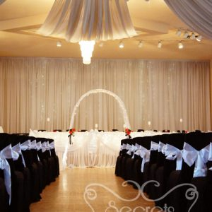 Chairs are Decorated in Black Fitted Polyester Chair Covers, with White Satin Sashes
