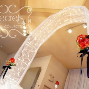 Wedding Arch, Decorated with Twinkle Lights, White Tulle, and Red Bouquet Pull-Backs