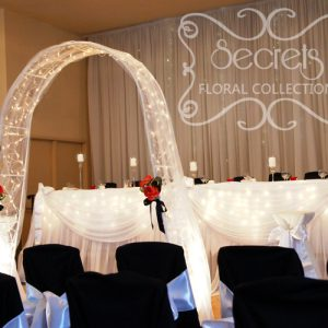 Backdrop and Tables are Decorated with White Sheer and Twinkle Lights to Achieve a Fairytale Look