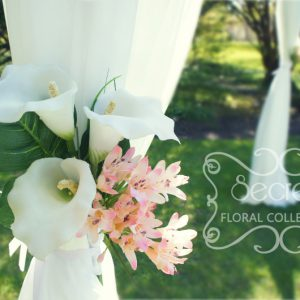 Close-up of the ceremony arch, with calla lilies arrangement
