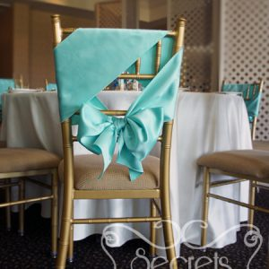 Close-up of chiavari chair, demonstrating how we have tied the Tiffany blue satin sashes in a unique way (diagonally)!