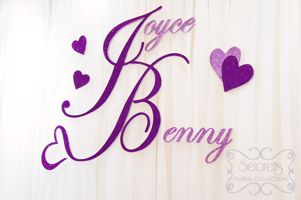 A crystallized royal purple and silver wedding reception decoration close up of purple glittery names designed with trailing heart junglespirit Gallery