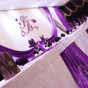 Head table decorated with white crinkled linen and purple satin stripes. Table edge is crystallized by adding our Bling! Bling! edge around the entire table