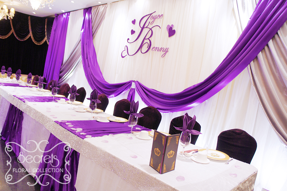 A crystallized royal purple and silver wedding reception decoration close up of backdrop lighted with white spotlights and swags are hold up junglespirit Image collections