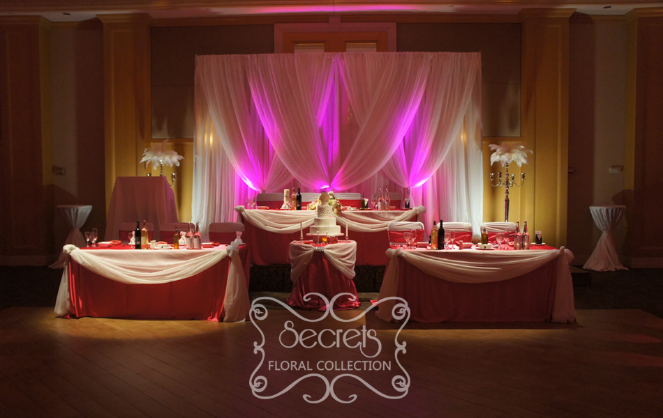 Setup Of The Cream Voile Backdrop With Fuchsia Led Uplights And Split Head Table