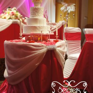Close up of cake tale, designed with fuchsia satin tablecloth base, and cream voile swags. Swag point is embellished with bling! bling! crystallized cuffs