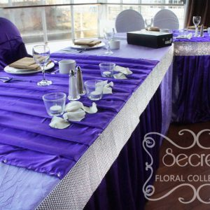 Close up up head table, with pleated royal purple stripes