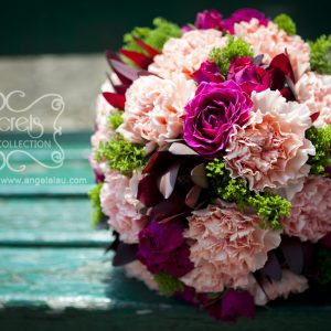 Fresh pink carnations, fuchsia spray roses, burgundy leucadendron, green trachelium bridal bouquet, embellished with ivory ribbon and gold crystal brooch (top view)