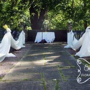 Outdoor ceremony with cream chiffon swags along the 2 sides of aisle