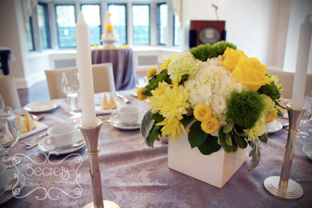 Low-profile centrepiece with fresh yellow roses, yellow cushion mums, green trick dianthus, light green carnations, succulents, cream hydrangea, yellow button mums, and dusty miller, in white cube pot (front angle)