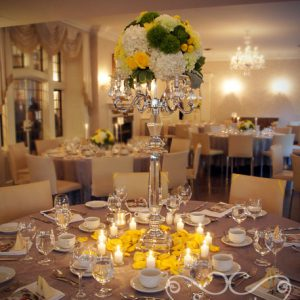 Head table centrerpiece of fresh yellow roses, yellow cushion mums, green trick dianthus, light green carnations, succulents, cream hydrangea, yellow button mums, and dusty miller, on real crystal candelabra. Surrounded with fresh yellow petals and votive candles