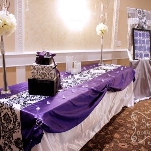 Receiving table with draped with purple overlay and damask runner. The easel is dressed up with damask fabric and crystal mesh ribbon - Toronto Wedding Decor Created by Secrets Floral Collection