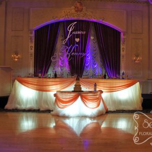 Head and cake tables with cream chiffon skirting, peach satin swags, and large crystal buckles - Toronto Wedding Decor Created by Secrets Floral Collection