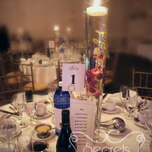 Two-tone fuchsia and peach dendobrium orchid centrepiece, with submerging flower and floating candle - Toronto Wedding Decor Created by Secrets Floral Collection