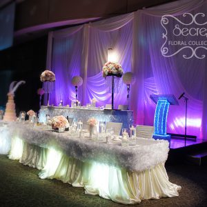 Parts of head table are dressed with ivory tablecloth and white ruffled trims - Toronto Wedding Decor Created by Secrets Floral Collection