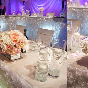 Low-profile head table arrangement with white, cream, and light pink flowers (roses, garden roses, peonies, hydrangea) in a modern mirrored vase - Toronto Wedding Decor Created by Secrets Floral Collection