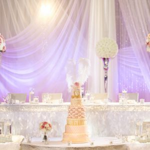 Part of the head table and cake tables are dressed with white ruffled table-skirt and crystallized bling wrap. Photo by Andes Lo Photography - Toronto Wedding Decor Created by Secrets Floral Collection