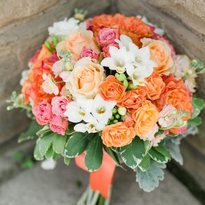 A colourful and vibrant bridal bouquet, with fresh coral garden roses (free-spirit), peach roses, stock flowers, white freesia, and spray roses - Toronto Wedding Flowers by Secrets Floral Collection
