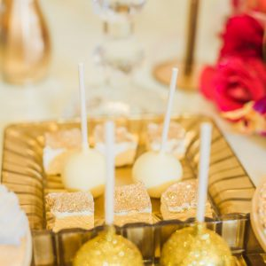 Detail shot of dessert tray at the Victorian Convention centre, Missisauga. Candy pops and dessert squares are accented with gold glitter. Decor by Secrets Floral.