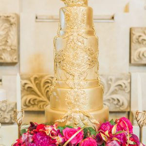 Gorgeous, gold wedding cake at the Victorian Convention centre, Missisauga. Decorated with real flowers at the bottom tier, such as hot pink gerbera daisy, fuscia dendrobium orchids, gold foliage, pink calla lily, hot pink rose. Flower and decor by Secrets Floral.