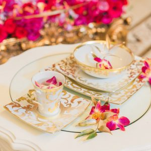 Close up shot of flat ware with individual blooms. Cinderella themed style shoot at the Victorian Convention centre, Missisauga. Flowers used are fuscia dendrobium orchids, hot pink gerber daisy, gold foliage. Flower and decor by Secrets Floral.