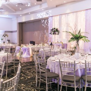 Wedding reception at Fontana Primavera, with tall centrepieces, purple tablecloths, and gold overlay linens. Toronto wedding flowers and decor by Secrets Floral.