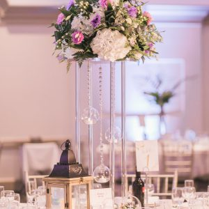 Fresh tall floral centrepiece arrangement, with cream hydrangea, purple lisianthus, and greenery. Suspending glass globes and rustic lantern at side. Toronto wedding flowers and decor at Fontana Primavera by Secrets Floral.