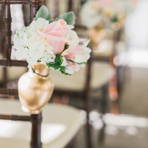 Fresh cream and blush pink wedding ceremony pew markers, with roses, hydrangea, and dusty miller in gold vases. Toronto wedding flowers by Secrets Floral.