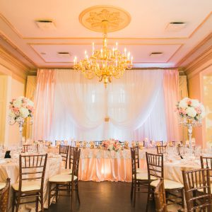 Wedding reception backdrop and head table in blush pink and gold. Toronto wedding decor at Graydon Hall by Secrets Floral.